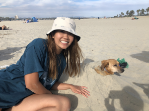 Christina, wearing a cream-colored bucket hat with butterflies next to Yoda, buried underneath the sand.