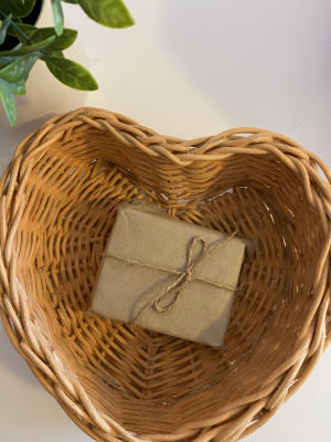body soap wrapped in brown paper and tied with twine, placed in a brown heart shaped basket